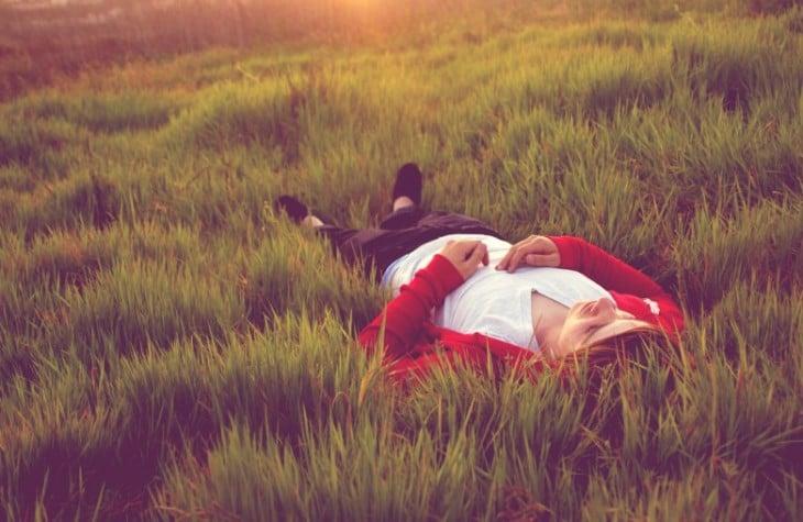 persona acostada sobre un pasto con un poco de sol
