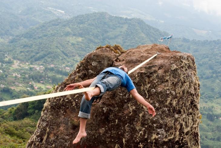 hombre acostado sobre una cuerda entre dos montañas