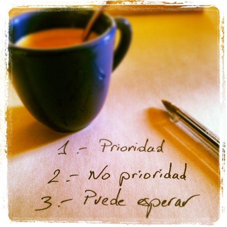 imagen de una taza de café con un papel y una pluma donde escribe prioridades