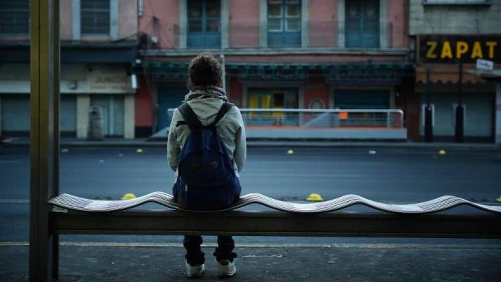 chica sentada en una banca esperando el autobús