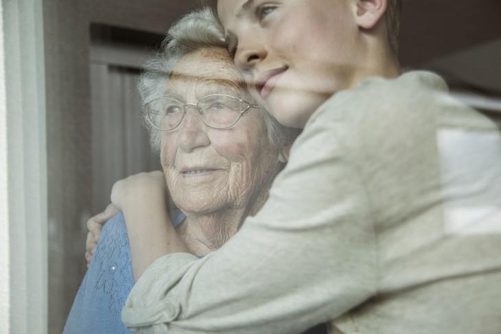 chica abrazando a su abuela a través de una ventana