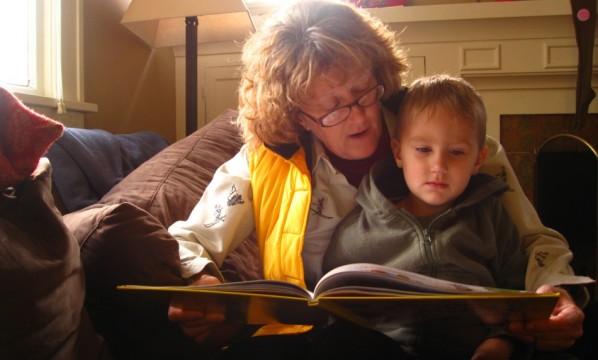 abuela leyendo un cuento a su nieto sentada sobre sus piernas