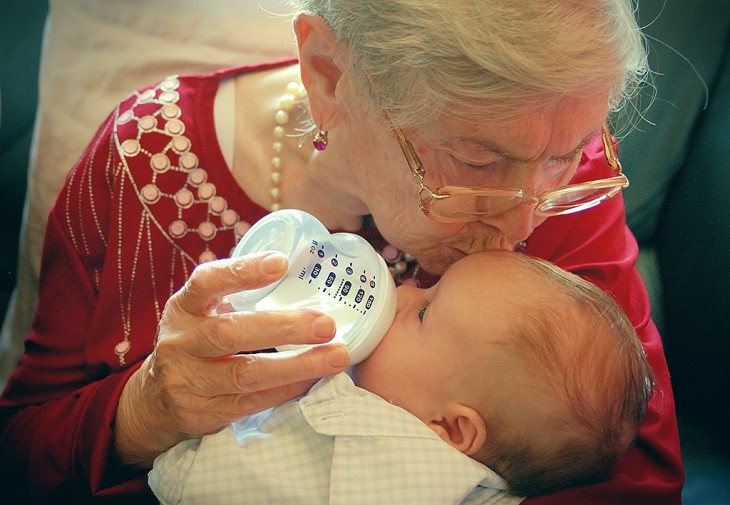Abuelita con su nieto en sus brazos dando un beso en su frente