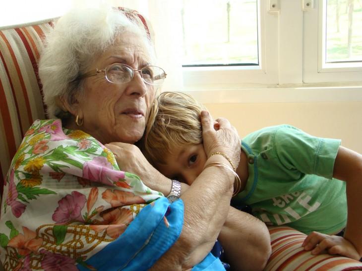 abuelita abrazando a su nieto sentada en un sillón