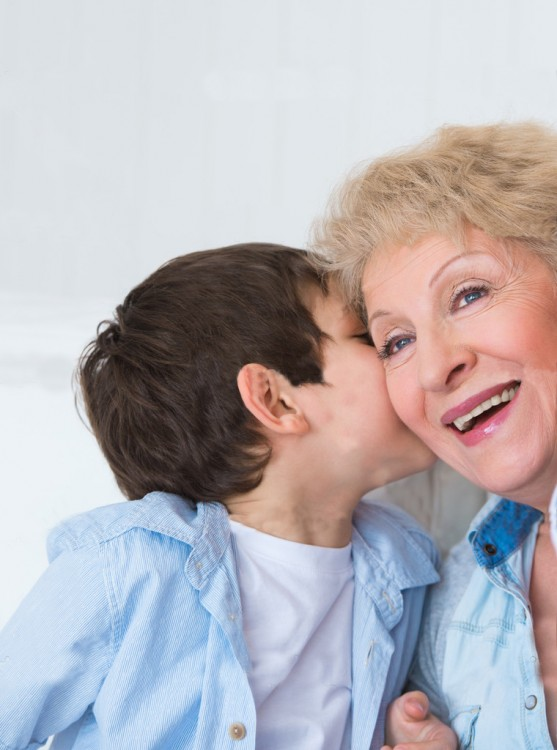 niño platicando al oído con su abuelita