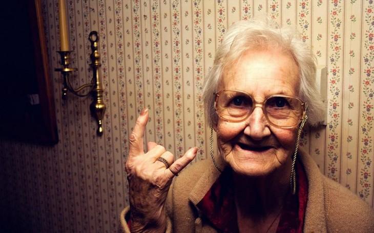 abuelita con la mano levantada haciendo señal de rock and roll