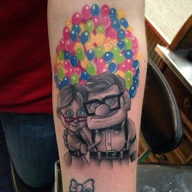 Tatuaje de los personajes de la película Up de Disney en un brazo
