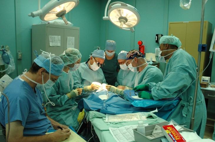 ayudantes quirúrgicos y médicos asistiendo a un médico durante una operación