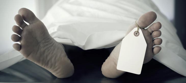 pies de una persona muerta acostada sobre una plancha