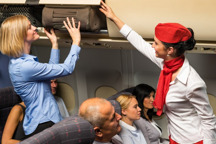 auxiliar de vuelo ayudando a una persona a acomodar su equipaje