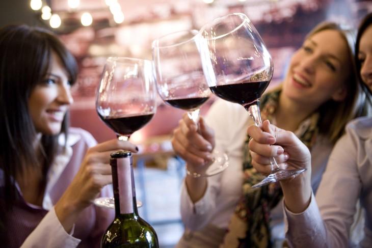 personas brindando con una copa de vino tinto