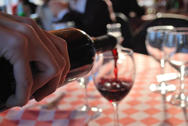 mano de una persona sirviendo una copa de vino tinto