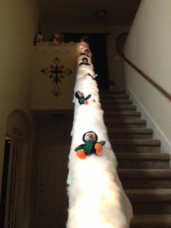 escalera decorada con pingüinos que van resbalándose por la nieve
