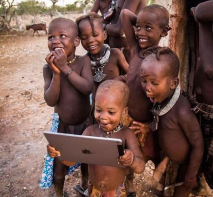 niños africanos felices por ver imagenes en un ipad