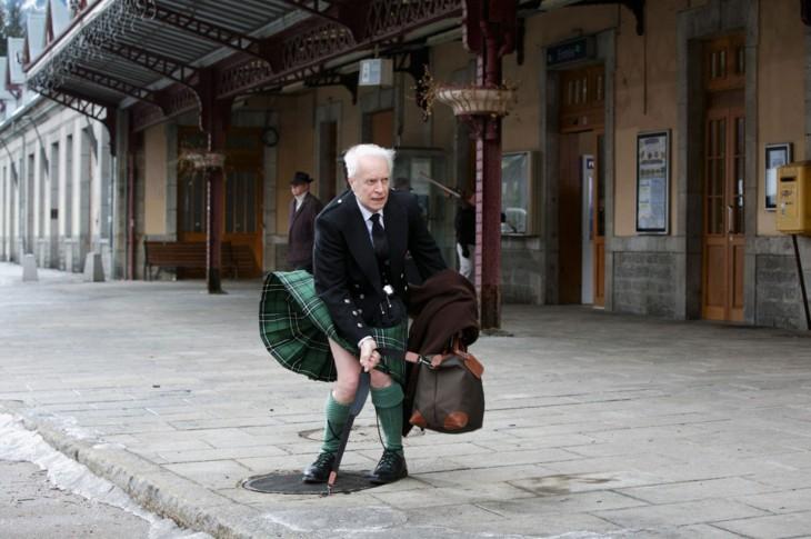 hombre escoces cuidandose de que no se le suba demasiado la falda