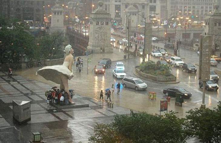 personas de chicago cubriendose de la lluvia en la falda de Marylin Monroe