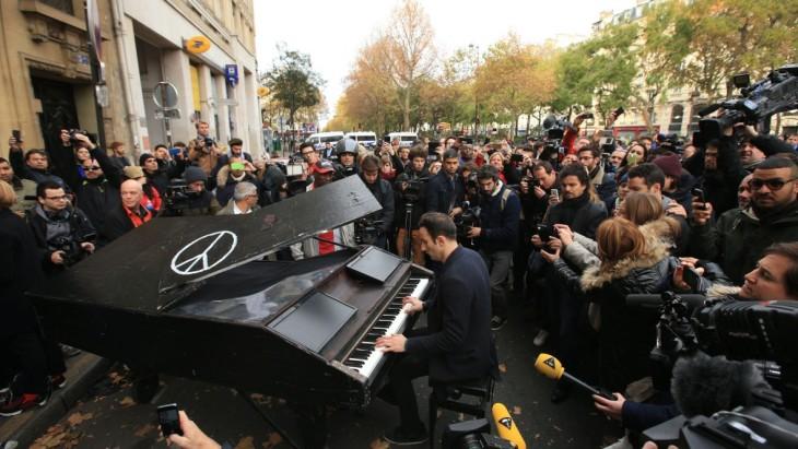 Hombre toca imagine de john lennon después del atentado en París en noviembre