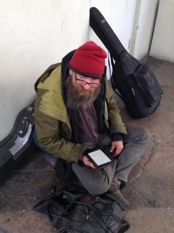 hombre sin hogar con tableta electrónica con cientos de novelas