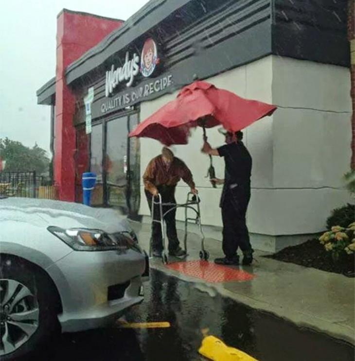 joven trabajador del wendys le ayuda a un anciano a caminar mientras llueve intenta cubrirlo