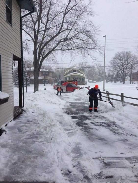 rescatistas ayudando a un anciano a quitar la nieve de su porche mientras él se encuentra en recuperacióm