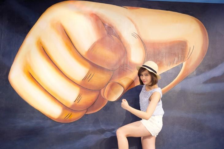 Chica japonesa a un lado de un puño dibujado en un museo de Hong Kong