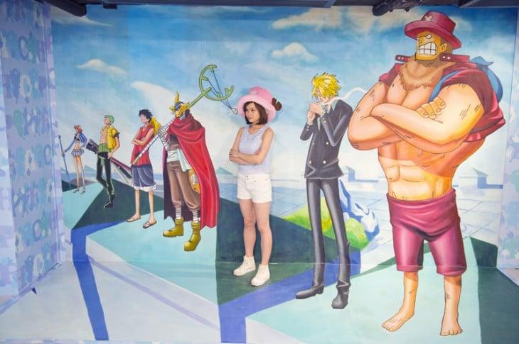 Chica dentro de una obra One Piece en el museo 3D en Hong Kong