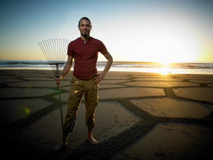 Andrés Amador con un rastrillo de jardín en una playa