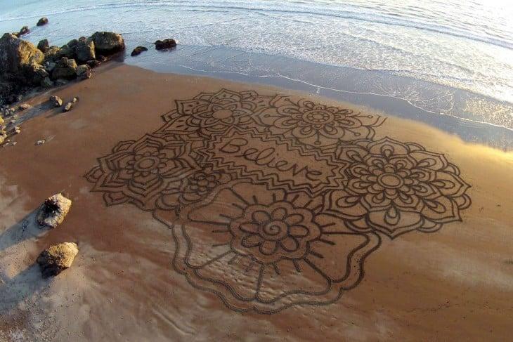 """Dibujo de flores con la palabra """"Believe"""" en la arena sobre una playa"""