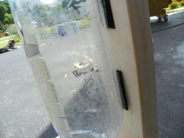 botella de plástico pegada a una tabla de madera