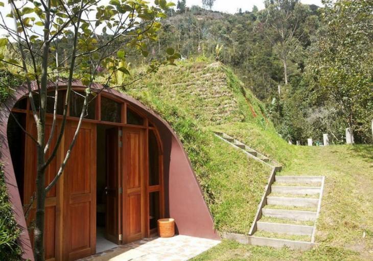 casa con puerta de madera al estilo hobbit rodeada de árboles