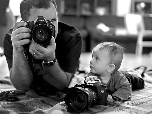 bebé con una cámara observando como su padre toma una fotografía