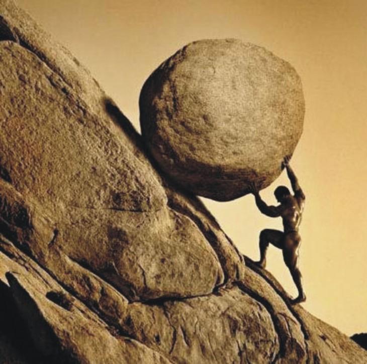 Imagen de una persona subiendo una roca por una montaña
