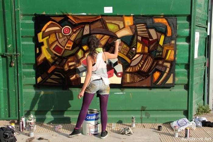 Chica pintando un cuadro sobre una pared