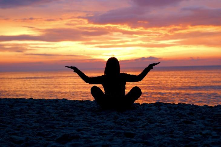 una mujer practicando yoga frente al mar al atardecer
