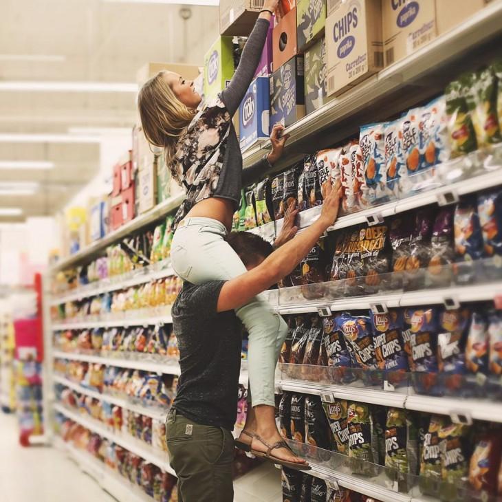 una chica sentada sobre los hombros de un chico para alcanzar una caja en un centro comercial