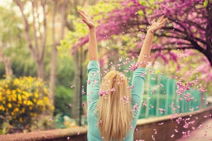 chica abriendo los brazos hacia arriba aventando hojas rosas