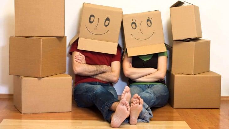 dos personas con cajas de caritas felices en su cabeza sentados sobre el suelo