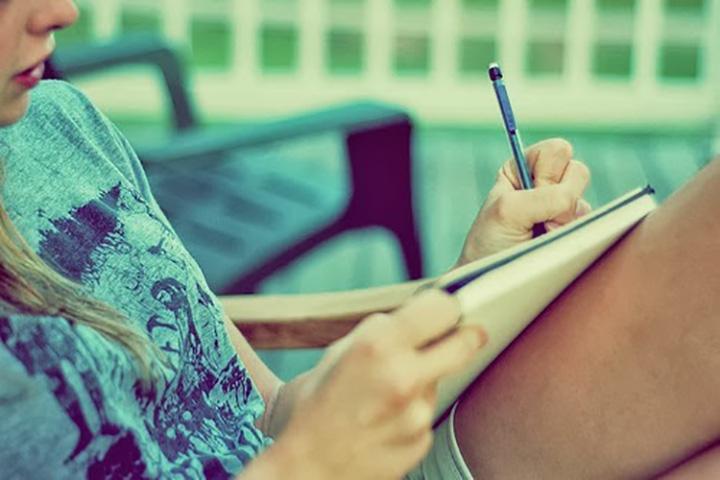 chica escribiendo sobre una libreta