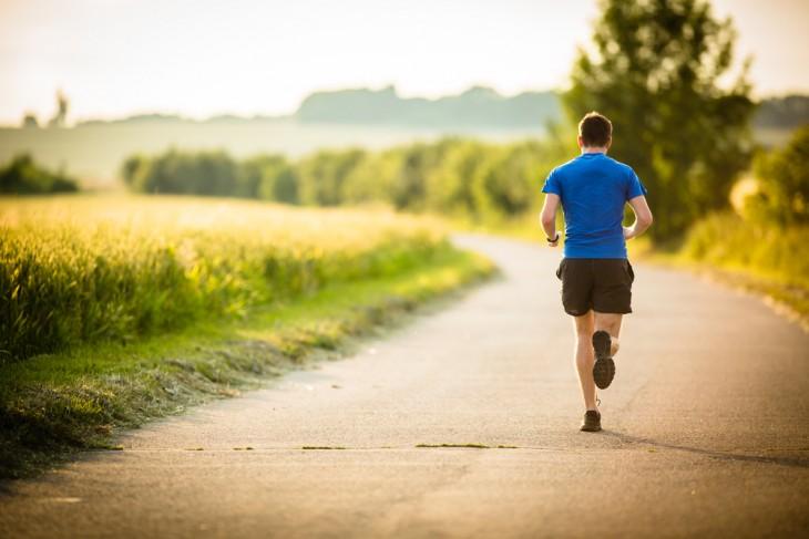 Fotografía de un chico corriendo por una carretera