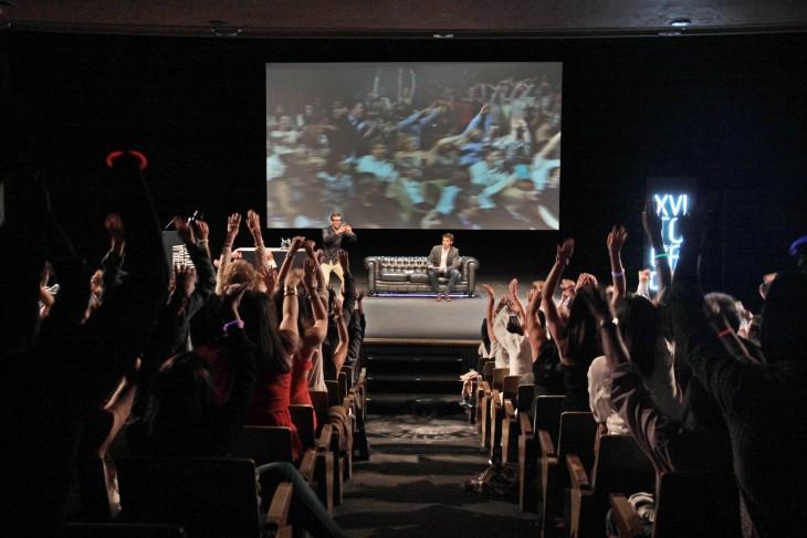 personas levantando la mano en un auditorio