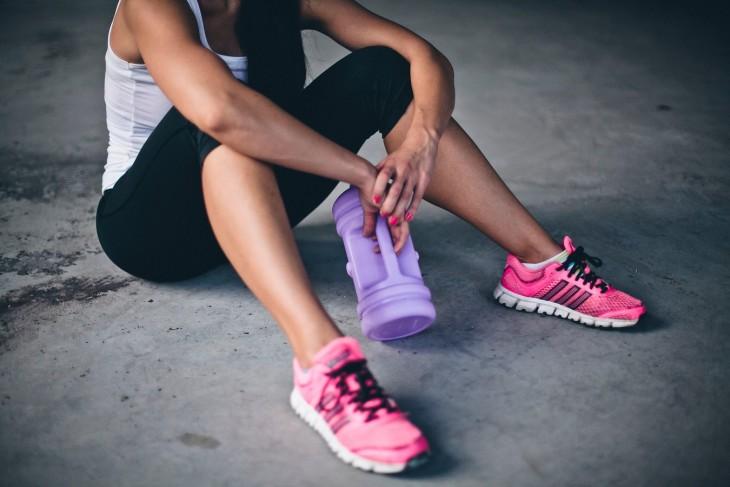 mujer con ropa deportiva sentada en el suelo con una botella de agua