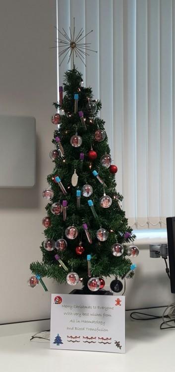 árbol navideño decorado con tubos de hematologia y esferas con fotografías de doctores