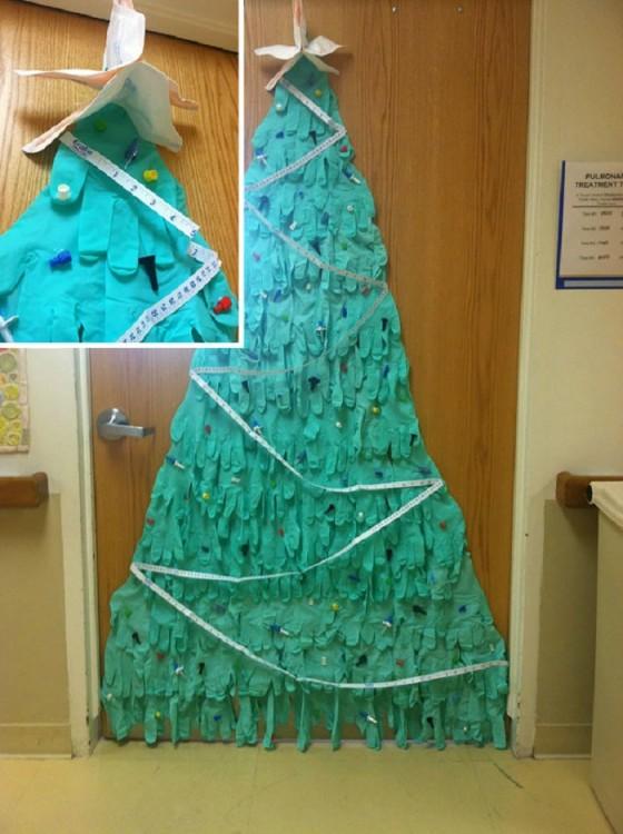 árbol de navidad hecho con guantes de látex pegado en una puerta