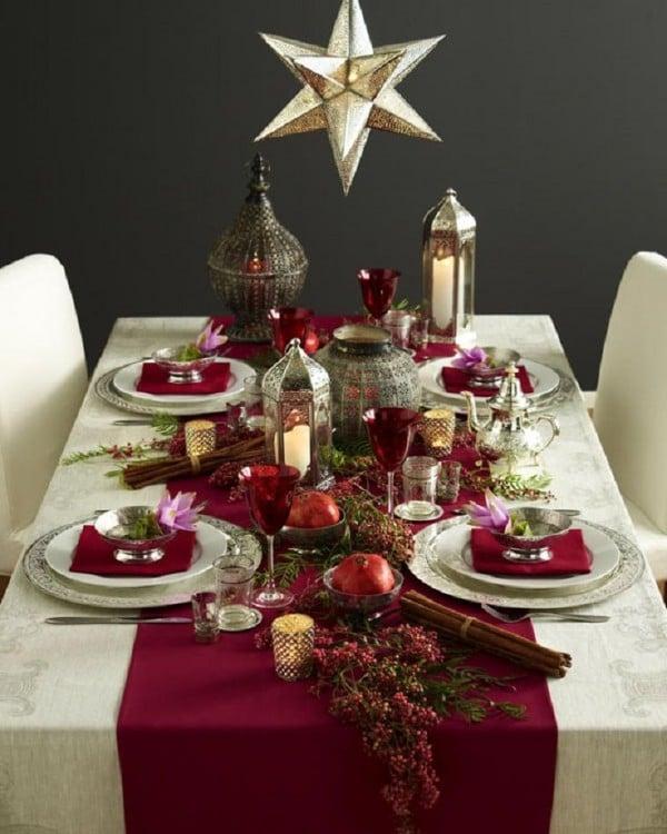 decoración de una mesa de navidad con copas, veladoras y frascos