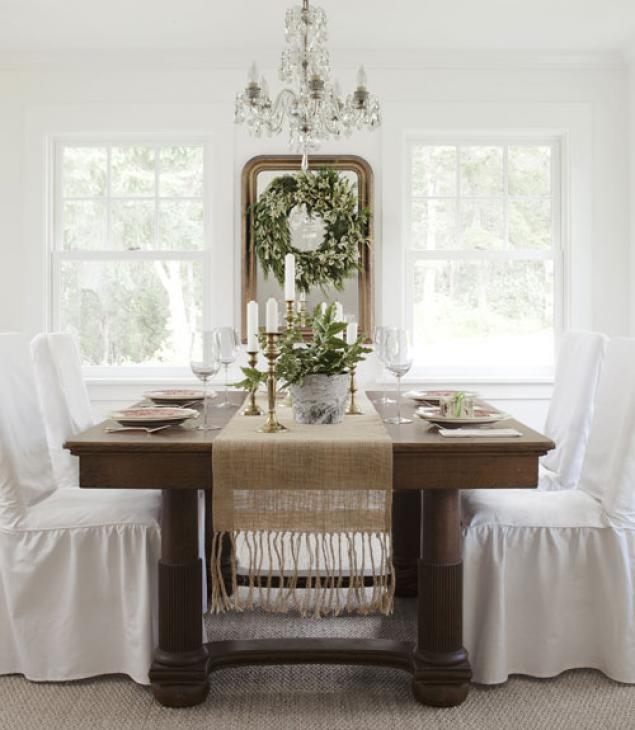 mesa de navidad adornada con velas y floreros con ramas verdes