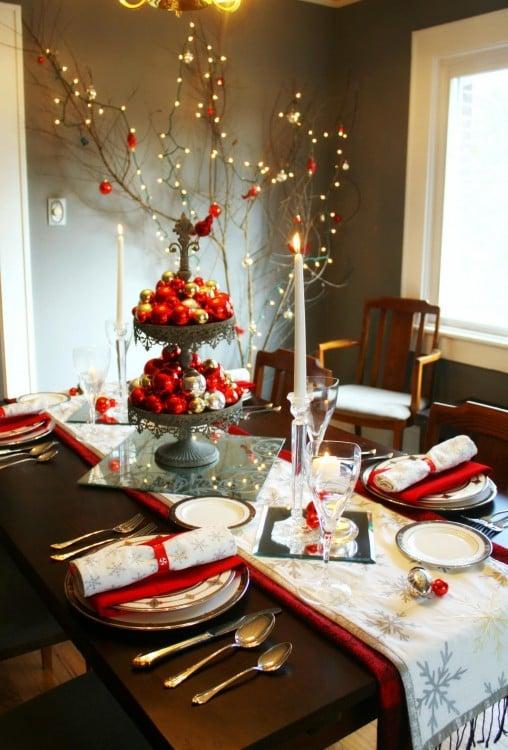 decoración de una mesa con velas y un centro para pastel con esferas