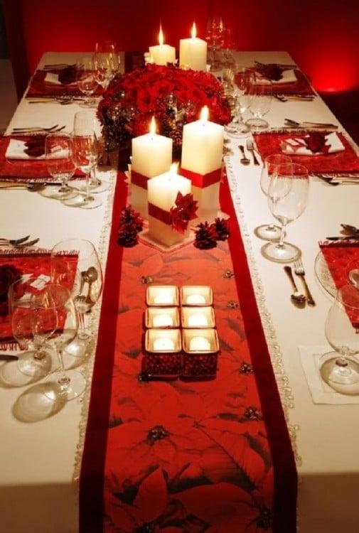 Mesa adornada con velas pequeñas y veladoras grandes cuadradas y en el centro un arreglo de flores en color rojo