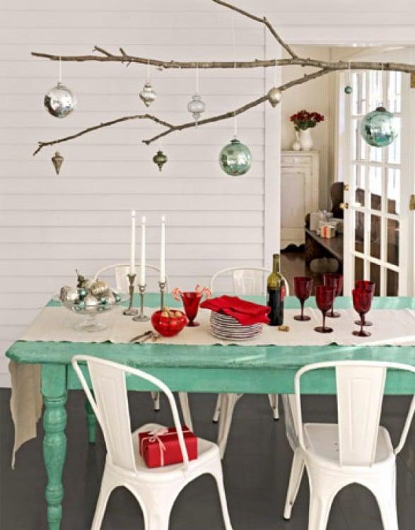 mesa de color azul decorada con copas de vino y ramas de las que cuelgan algunas esferas