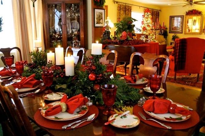 mesa de navidad decorada con velas y uvas con ramas en color verde a