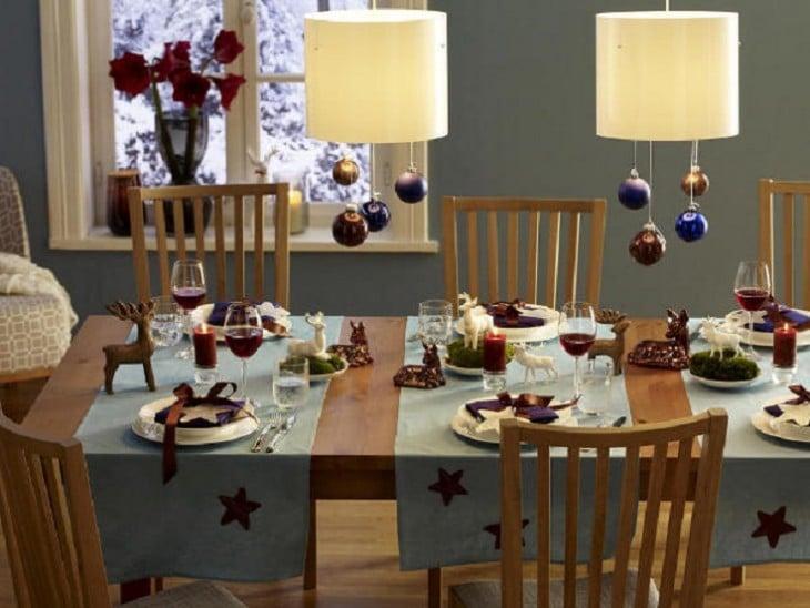 mesa decorada con esferas colgando de las luces con copas y ciervos de centros de mesa